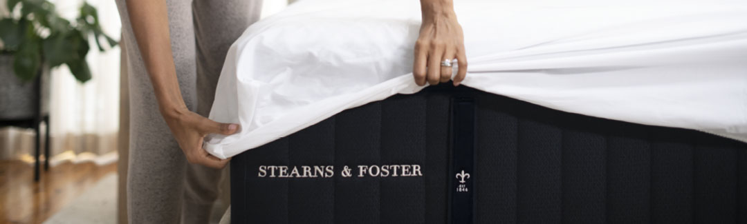 Woman putting sheets on a Stearns & Foster mattress